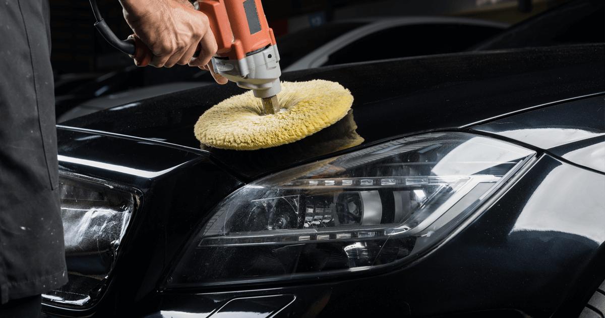 Car body shop. Car detailing, man polishing a black car