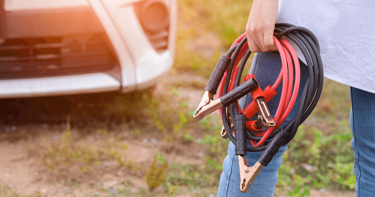 Woman is holding car battery jump leads, getting ready to jump start a car