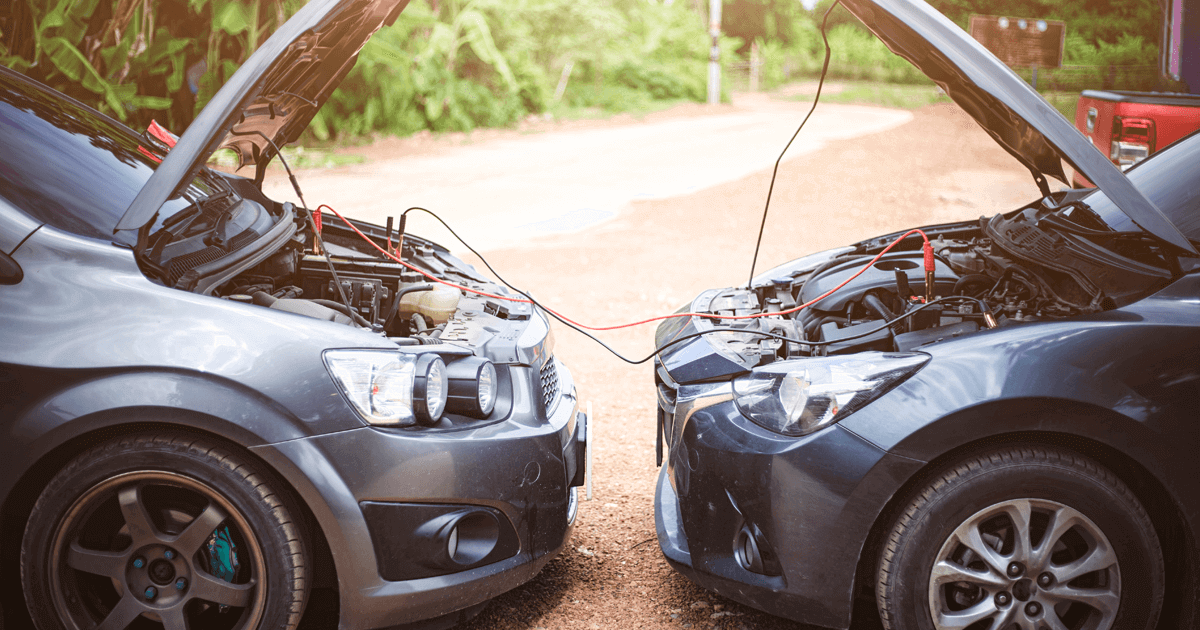 Jumper cables being used to jump start another car outdoor